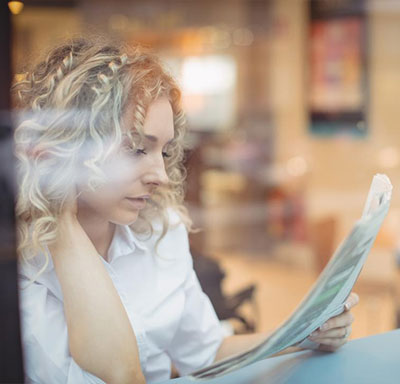 Woman-reading-a-newspaper-in-a-shop-window